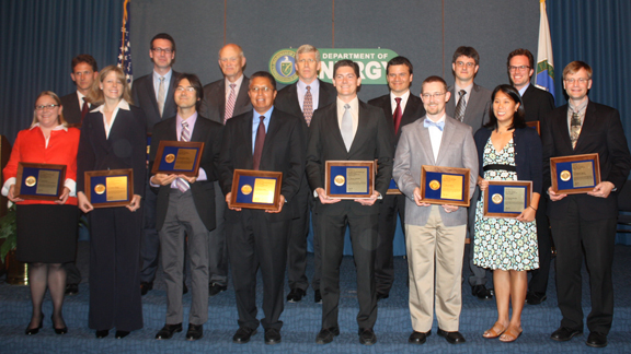 2011 PECASE winners holding their awards standing with DOE leadership on a stage (Ceremony: 8/1/12).