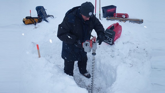 Alex Kholodov (University of Alaska, Fairbanks) uses an electric auger to prepare holes for water wells at NGEE Arctic Sites in Barrow, Alaska.