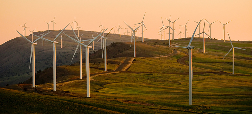 Wind farm on hilly terrain against a setting sun
